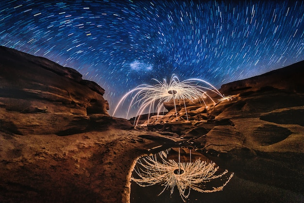 Burning steel wool on the rock with milky way near the river at sam phan bok in ubonratchathani unseen in thailand. the grand canyon of thailand. Premium Photo