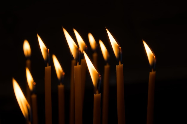Burning wax candles against the window in a dark room Premium Photo