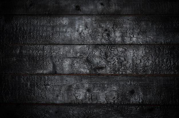 Сгоревший деревянный фон. горизонтальные черные доски Premium Фотографии