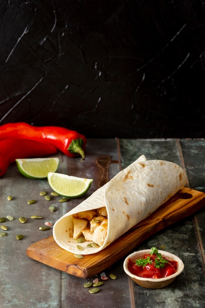 Burrito on cutting board near peppers, lime and tomato sauce against black background Free Photo