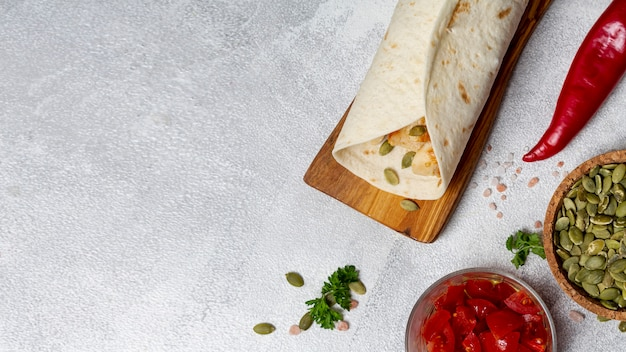 Burrito near peppers, cardamom seeds and sliced tomatoes Free Photo
