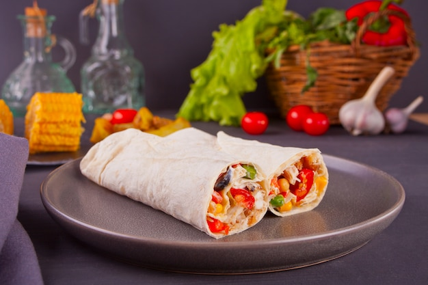 Burrito rolls with vegetables on black table and vegetables, cherry tomatoes and garlic at background Premium Photo