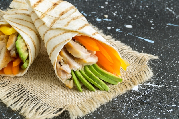 Burrito with grilled chicken and vegetables (fajitas, pita bread, shawarma) Premium Photo