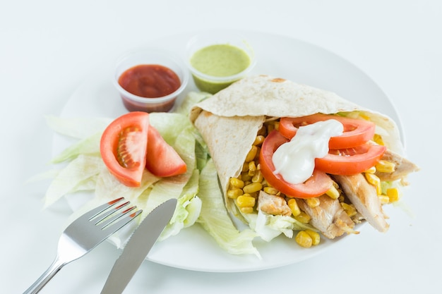 Burrito wrap with tomato, corn, lettuce, chicken, mayonnaise and sauces with white background Premium Photo