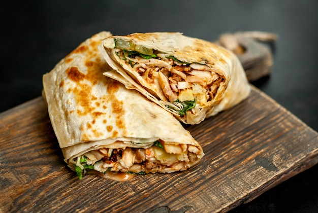 Burrito wraps with chicken and vegetables on a cutting board, against a background of concrete, mexican shawarma Premium Photo