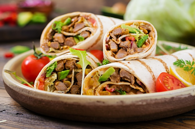 Burritos wraps with beef and vegetables on wood. beef burrito , mexican food. healthy food background. mexican cuisine. Premium Photo