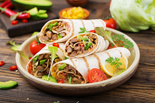 Burritos wraps with beef and vegetables on a wooden background. beef burrito , mexican foo Premium Photo