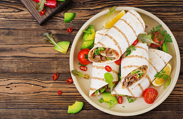 Burritos wraps with beef and vegetables on a wooden table. beef burrito , mexican food. mexican cuisine.top view. Premium Photo