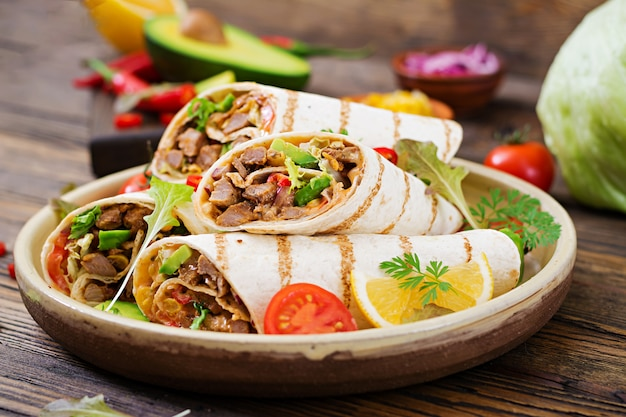 Burritos wraps with beef and vegetables on a wooden table. beef burrito , mexican food. mexican cuisine. Premium Photo