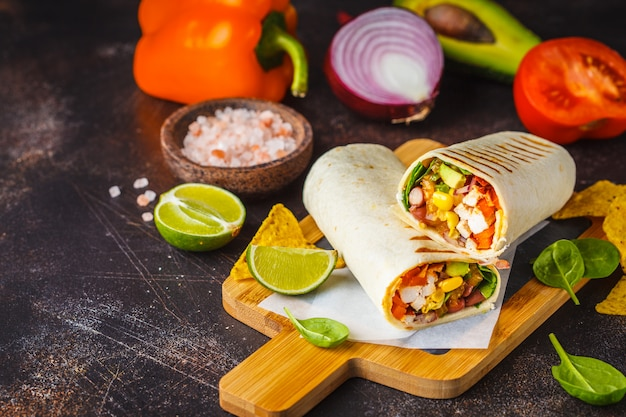 Burritos wraps with chicken, beans, corn, tomatoes and avocado on wooden board, dark background. Premium Photo