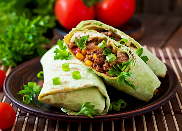 Burritos wraps with minced beef and vegetables on a wooden surface Free Photo