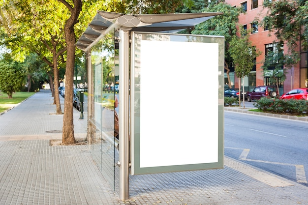 Bus stop billboard in green city Free Photo