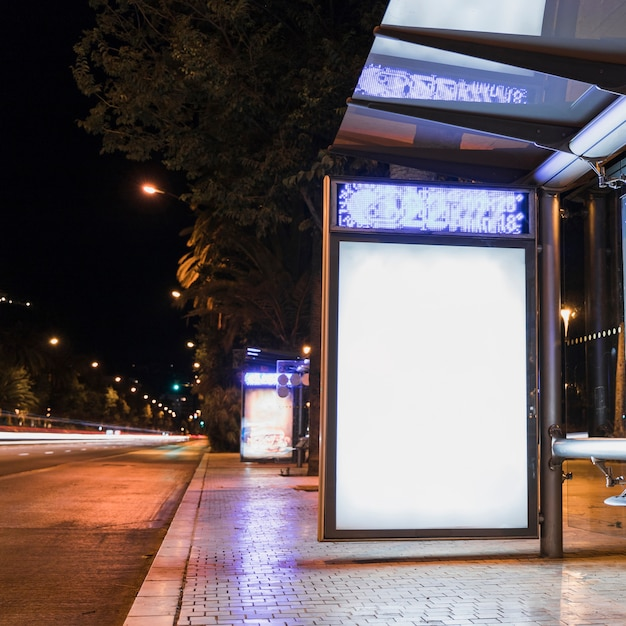 Bus stop with blank advertising billboard near street in city Free Photo