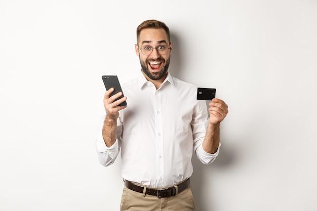 ビジネスおよびオンライン決済。携帯電話とクレジットカードで支払う興奮した男、驚いて笑って、立っている 無料写真