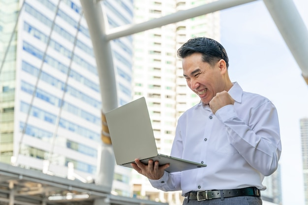 Business asian man using laptop computer on business district urban - lifestyle business people concept Free Photo