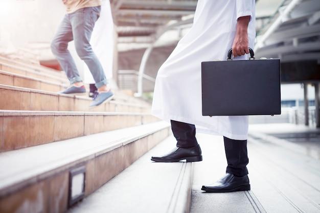 ビジネスの背景のコンセプト。アラブのビジネスマン、ビジネスバッグ、階段を上って歩く Premium写真