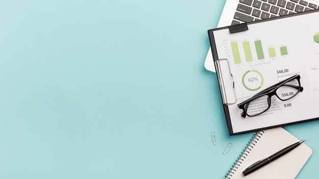Business budget chart and eyeglasses on laptop with spiral notepad and pen against blue background Free Photo