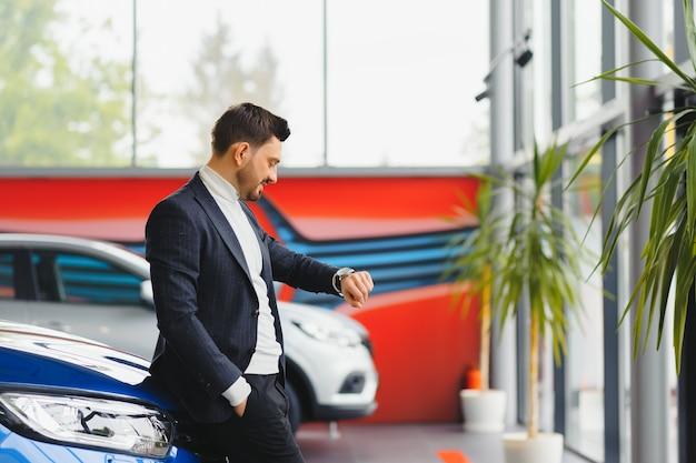 비즈니스, 자동차 판매, 소비 및 사람들 개념-자동 표시 또는 살롱 배경 위에 행복한 사람 프리미엄 사진