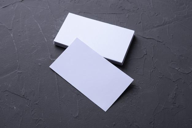 Пустая визитная карточка на фоне рок бетон. корпоративные канцелярские товары, фирменный макет. креативный дизайнерский стол. плоская планировка. скопируйте место для текста. шаблон для удостоверения личности. Premium Фотографии