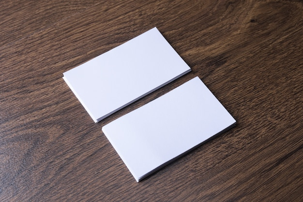 Пустая визитная карточка на деревянных фоне. корпоративные канцелярские товары, фирменный макет. креативный дизайнерский стол. плоская планировка. скопируйте место для текста. шаблон для удостоверения личности. Premium Фотографии