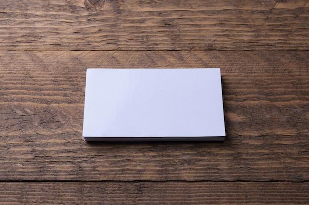 木製の壁に空白の名刺。コーポレートステーショナリー、クリエイティブデザイナーデスク。フラットレイ。テキスト用のスペースをコピーします。 Premium写真