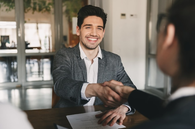 Business, career and placement concept - happy caucasian man 30s rejoicing and shaking hands with employee, when was recruited during interview in office Premium Photo