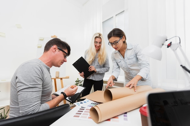 Business colleagues looking on cardboard sheet Free Photo