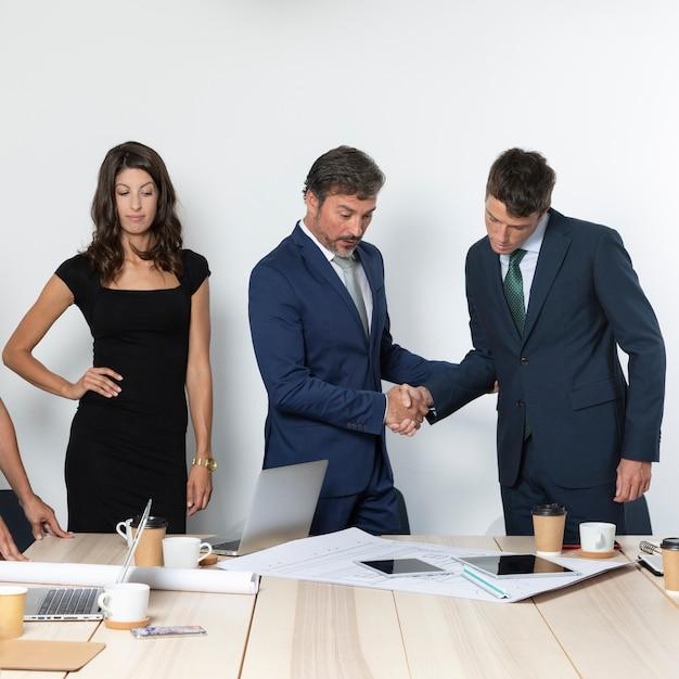 Colpo medio dei colleghi di affari che stringono le mani Foto Gratuite