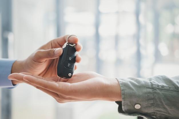 ビジネスコンセプト、自動車保険、自動車の販売と購入、自動車ローン、自動車販売契約の車のキー。新しい所有者は男性の営業担当者から鍵を取っています。 Premium写真