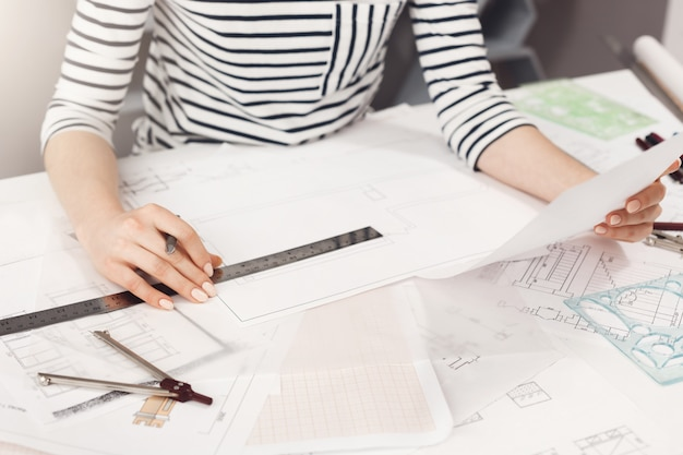Business concept. close up detail of young successful architect entrepreneur in striped clothes sitting at white table, looking through work plan, holding pen and ruler in hands, working in new busine Free Photo