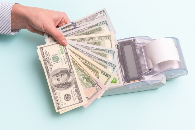 Business concept. close-up of a female hand holding several hundred dollar bills above the cash register to pay for a product or service Premium Photo