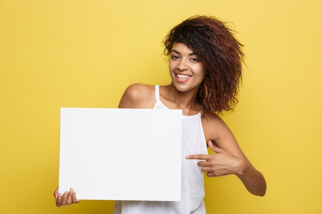 Business concept - close up portrait young beautiful attractive african american smiling showing plain white blank sign. yellow pastel studio background. copy space. Free Photo
