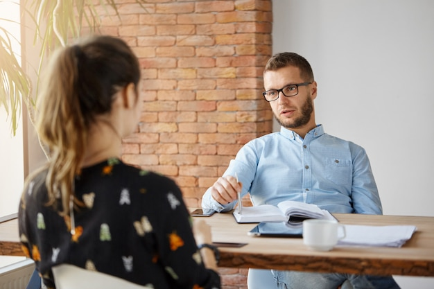Business concept. dark-haired anonymous woman sitting at table in office in front of serious mature human resources manager, speaking about work responsibilities during job interview. Free Photo