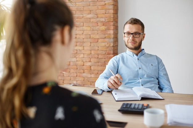 Business concept. job interview. adult bearded male hr manager in glasses and shirt sitting in light office in front of brunette caucasian woman, asking questions about previous work place Free Photo