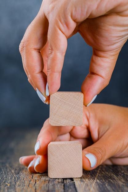 Бизнес-концепция на темном и деревянном фоне вид сбоку. руки, упорядочивая деревянный куб как стопку. Бесплатные Фотографии