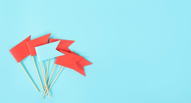 Business concept. reaching the goal. a blue flag stands out from the red flags on a blue table. to be different.  copy space. Premium Photo