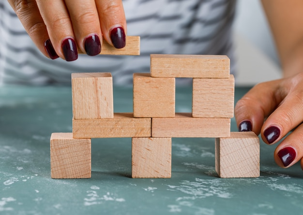 ビジネスコンセプトの側面図です。女性が木製のブロックからタワーを構築します。 無料写真