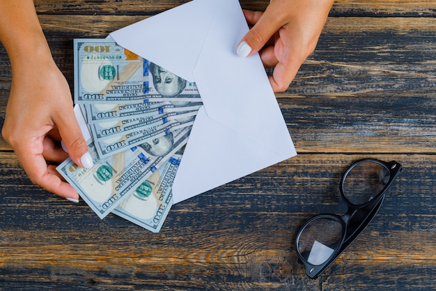 Бизнес-концепция с очками и конверт с деньгами на деревянной поверхности Бесплатные Фотографии