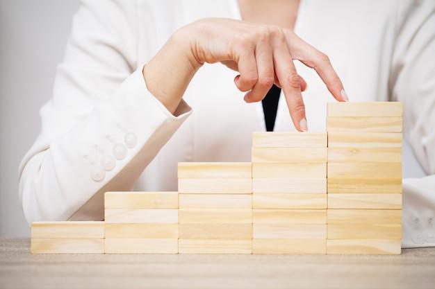 ビジネスコンセプトは、女性の手が会社の成功を象徴する木製の立方体を作る Premium写真