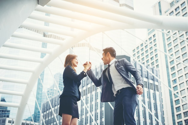 Business couple hands up doing yes outdoor. concept of teamwork Free Photo