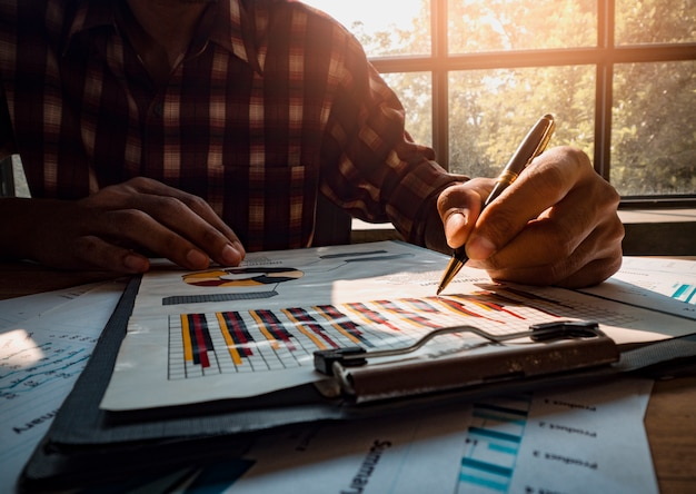 Business designer is holding a pen to write a successful investment income graph. Premium Photo