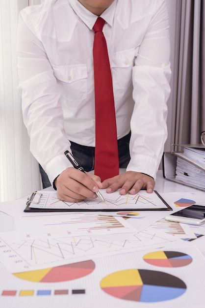 Business documents on office table with smart phone and digital tablet and man working Premium Photo