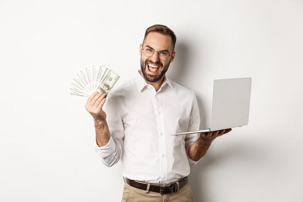 Affari ed e-commerce. uomo d'affari emozionante che tiene soldi dollari e laptop, lavorando online, in piedi Foto Gratuite