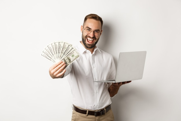Business and e-commerce. happy successful businessman bragging with money, working on laptop online, standing Free Photo