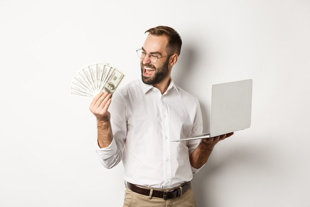 Business and e-commerce. successful businessman using laptop for work and holding money, standing Free Photo