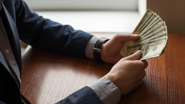 Business executive in formal suit giving money as a bribe Premium Photo
