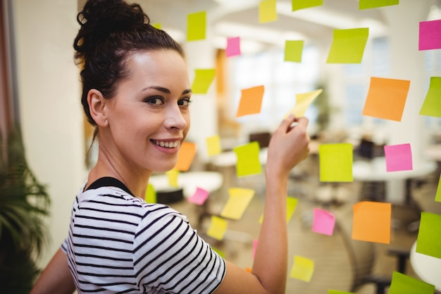 Business executive sticking sticky notes Free Photo