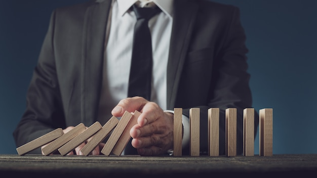 Business executive stopping collapsing dominos with his hand Premium Photo