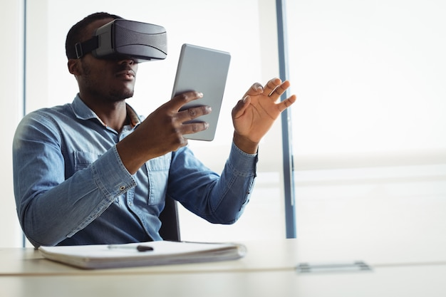 Business executive using virtual reality headset and digital tablet Free Photo