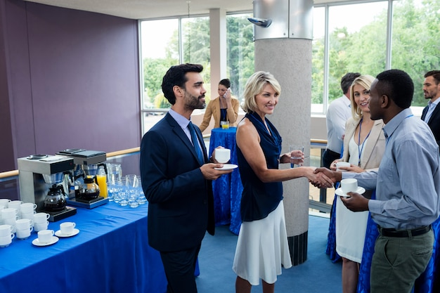 Business executives interacting with each other while having coffee Premium Photo